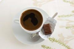 En kopp kaffe med en godis Arkivbild