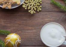 En kopp kaffe med ett tjockt skum, julkakor med socker och kanel och julpynt royaltyfria foton