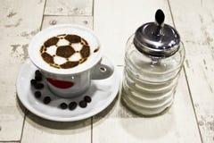 En kopp kaffe med fotbollbollen Royaltyfria Bilder