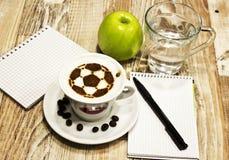 En kopp kaffe med fotbollbollen royaltyfria foton