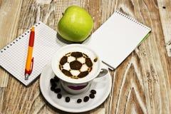 En kopp kaffe med fotbollbollen Arkivbild