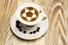 En kopp kaffe med fotbollbollen Royaltyfri Fotografi