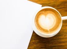 En kopp kaffe med hjärtaform och öppnar den tomma boken fotografering för bildbyråer