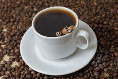 En kopp kaffe med kaffebönor arkivfoton