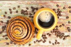 En kopp kaffe med kanelbulle arkivfoton