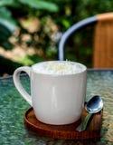 En kopp kaffe med kräm- och vit choklad flagar Royaltyfri Fotografi