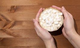 En kopp kaffe med mjölkar och marshmallowen I hand royaltyfria bilder