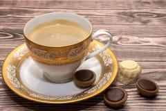 En kopp kaffe med sötsaker Arkivbild