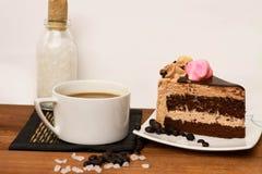 En kopp kaffe med skivan av chokladkakan Arkivbild