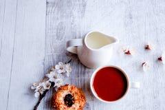 En kopp kaffe, mjölkar och kakan på en grå bakgrund royaltyfria foton