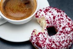 En kopp kaffe och en biten munk arkivfoton