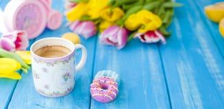 En kopp kaffe och donuts på en blå träbakgrund Bukett av blommor guling och rosa färger Den rosa klockan är som en cykel Arkivbilder
