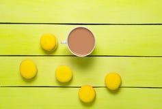 En kopp kaffe och gulingmakron på en blå trätabell Tre royaltyfria foton
