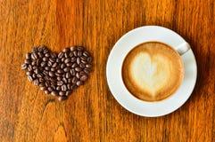 En kopp kaffe- och kaffeböna med hjärta formar Arkivbilder