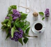 En kopp kaffe och lilor på tabellen arkivfoton