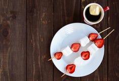 En kopp kaffe och marshmallower med nya jordgubbar på steknålar royaltyfria foton