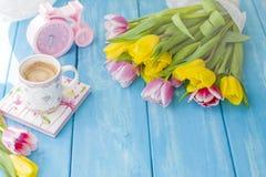 En kopp kaffe på en anteckningsbok på en blå träbakgrund Ljust färgar Bukett av blommor guling och rosa färger Den rosa klockan ä Arkivbild