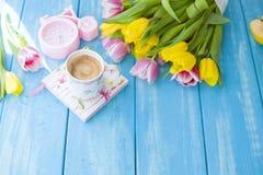 En kopp kaffe på en anteckningsbok på en blå träbakgrund Ljust färgar Bukett av blommor guling och rosa färger Den rosa klockan ä Royaltyfri Fotografi