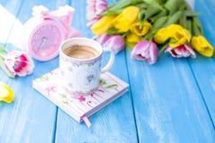 En kopp kaffe på en blå träbakgrund Bukett av blommor guling och rosa färger Den rosa klockan är som en cykel blå molnig fjäder f Arkivfoton