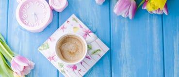 En kopp kaffe på en blå träbakgrund Ljust färgar Bukett av blommor guling och rosa färger Den rosa klockan är som en cykel Arkivbilder
