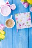 En kopp kaffe på en blå träbakgrund Ljust färgar Bukett av blommor guling och rosa färger Den rosa klockan är som en cykel Royaltyfri Bild