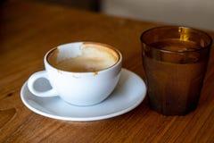 En kopp kaffe på den gamla trätabellen i kafékaffeavbrott i morgon arkivfoto
