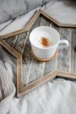 En kopp kaffe på ett skandinaviskt trästjärna-format magasin Arkivfoton