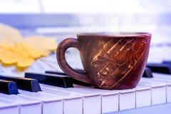 En kopp kaffe på pianotangenterna Lunch under ett avbrott på en mus arkivfoton