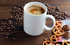 En kopp kaffe på en trätabell, korn av kaffe, choklad och kakor fotografering för bildbyråer