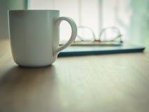 En kopp kaffe på trätabellen Enkel workspace hemma Fotografering för Bildbyråer