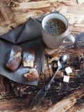En kopp kaffe, sockrar och metallskeden, kex som strilas med socker på en servett Arkivfoton