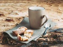 En kopp kaffe, sockrar och metallskeden, kex som strilas med socker på en servett Arkivfoto