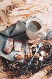 En kopp kaffe, sockrar och metallskeden, kex som strilas med socker på en servett på en trätabell Royaltyfria Bilder