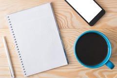 En kopp kaffe, en telefon och en anteckningsbok på en träbakgrund Arkivfoto