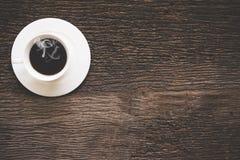 En kopp kaffemorgon på den gamla trätabellen Royaltyfri Bild