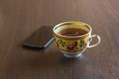 En kopp med ett te och en mobiltelefon på träbakgrunden Arkivfoto