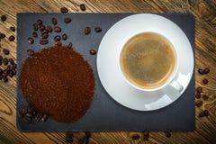 En kopp med kaffe, jordkaffe och kaffebönor Royaltyfri Bild