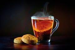 En kopp med svart te och citronen, kakor royaltyfria foton