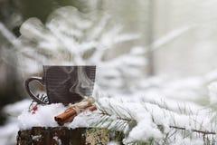 En kopp med en varm drink i den varma kakao för vinterskog med cinn royaltyfri bild