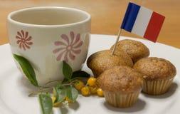 En kopp och banankakor med den lilla flaggan Arkivfoton