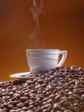 En kopp och en coffe med skum på bakgrunden av cjffeebönor Arkivbild