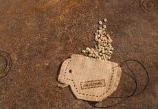 En kopp som mycket sys i jute av kaffebönor Arkivfoton