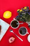 En kopp te, citron på en röd bakgrund, mat och drink, kniv och gaffel, tetid, sikt för frukosttid från över, kopp av coffe, r Royaltyfria Bilder