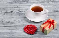 En kopp te, en gåvaask med en pilbåge och röd korall pryder med pärlor på en grå bakgrund kopiera avstånd Royaltyfri Fotografi