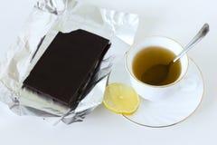 En kopp te i en vit kopp och en biten stång av mörk choklad arkivfoto