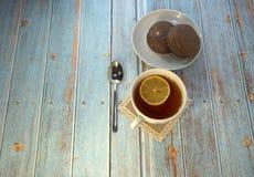 En kopp te med citronen, en sked och två chokladkakor på en plattalögn på en trätabell royaltyfri foto
