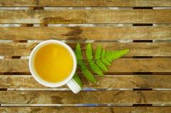 En kopp te med det gröna bladet på trätabellen Royaltyfria Bilder
