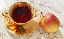 En kopp te med ett äpple arkivfoton