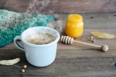 En kopp te nära den lantliga stack varma höst- eller vinterhalsduken på brun träbakgrund royaltyfri bild