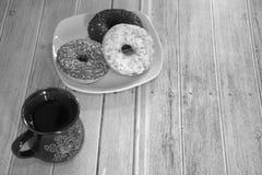 En kopp te och donuts i isläggningen på en plattalögn på tabellen svart vitskott N?rbild arkivfoton